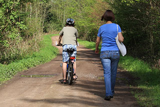 A cyclist and person walking sharing the trail