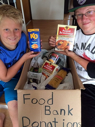 Two children holding food from a box for the food bank