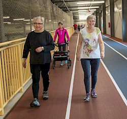 Photo of 3 women walking the track and smiling