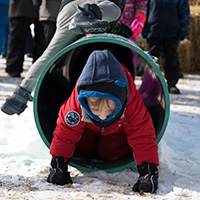 Kid crawling through tunnel at Fire and Ice Festival