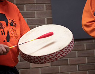 A participant plays a traditional drum