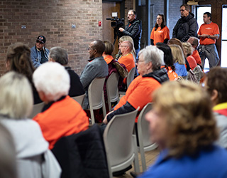 A orange shirt wearing crowd gather to listen to the Mayor