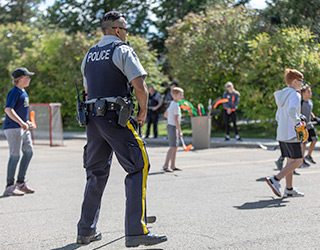 Municipal enforcement officer playing street hockey with kids