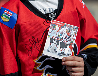 Child standing holding autographed picture and wearing autographed Calgary Flames jersey
